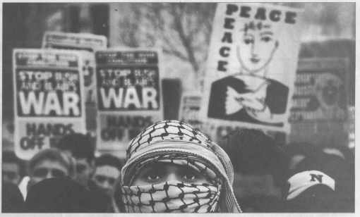 From 'The Independent on Sunday' 3 March 2002, page 4: image of a woman's head covered in cloth, only eyes visible and a few out-of-focus placards behind her.
