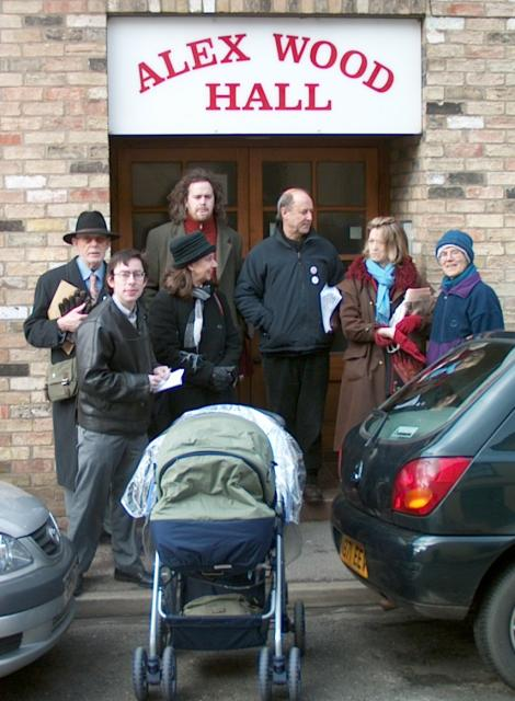 Seven people and a pram outside a doorway in city street