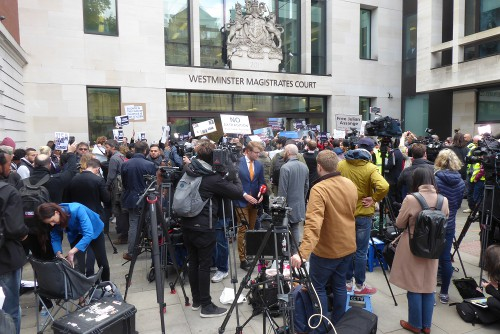 Court building behind with a crowd in front including placards and camera tripods.