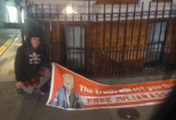 Man crouched next to long banner on pavement at night, with brick building and railings with candle behind