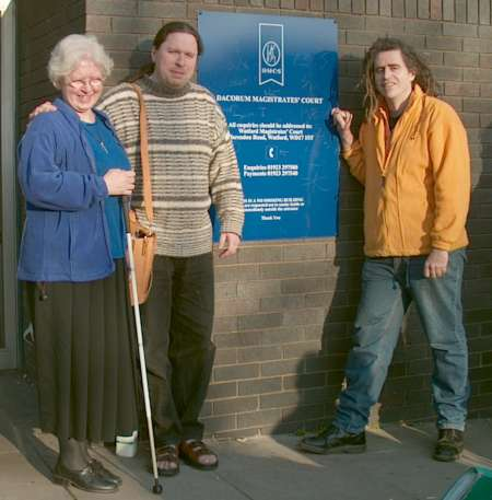 Three people standing by a brick wall with a blue sign