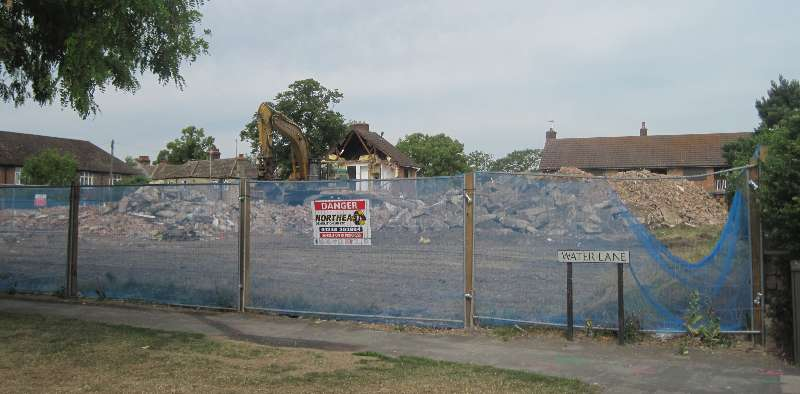 """WATER LANE"" on a street sign, with a mesh fence and visible beyond that a ridge of rubble up to about 10 feet high and the yellow arm of one earth-moving machine"