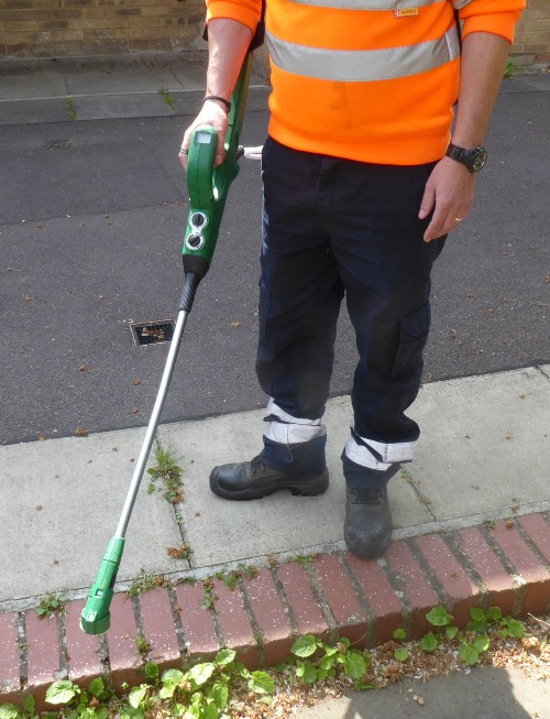 metal pole about 3 feet long with green plastic handle held by man wearing boots, work trousers and fluorescent jacket.