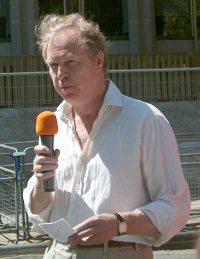 Man outside holding a microphone and small slip of paper